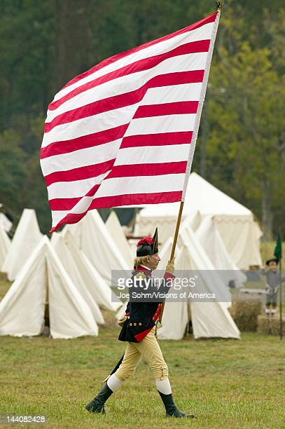 An early American flag is flown by solider on his way to Surrender Field at the 225th Anniversary of the Victory at Yorktown a reenactment of the...