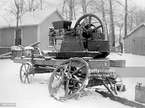An early gas engine sits on a wagon in the snow ca 1905