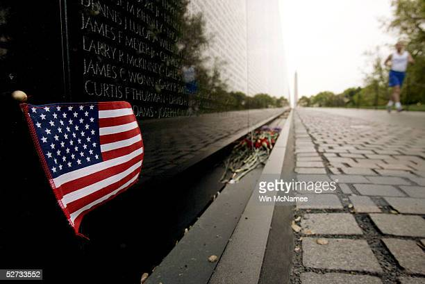 An early morning jogger runs past an American flag left in remembrance to Americans killed in Vietnam at the Vietnam Veterans Memorial on April 29...