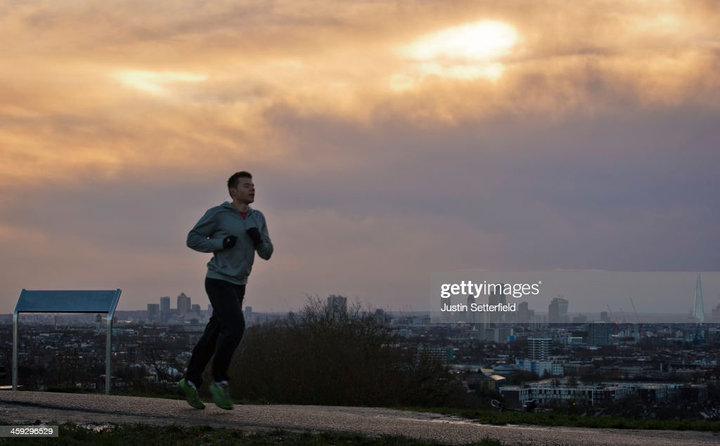 An early morning jogger runs through Hampstead Heath at dawn as the London skyline can be seen in the distance on December 25, 2013 in London, England. Christmas plans have been badly affected for thousands of people after storms across the UK have resulted in flooding, power cuts and significant problems with transport infrastructure.