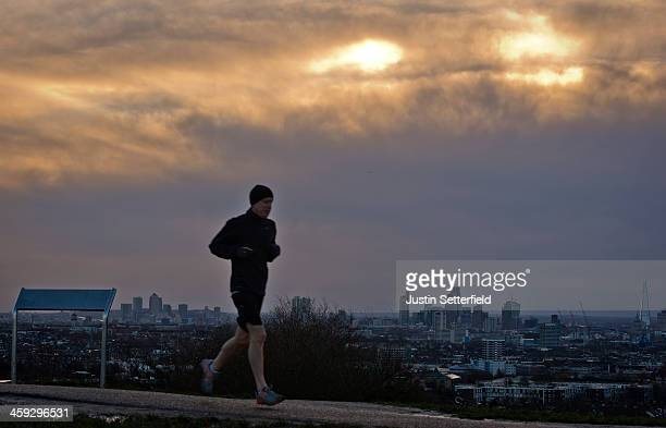 An early morning jogger runs through Hampstead Heath at dawn as the London skyline can be seen in the distance on December 25 2013 in London England...
