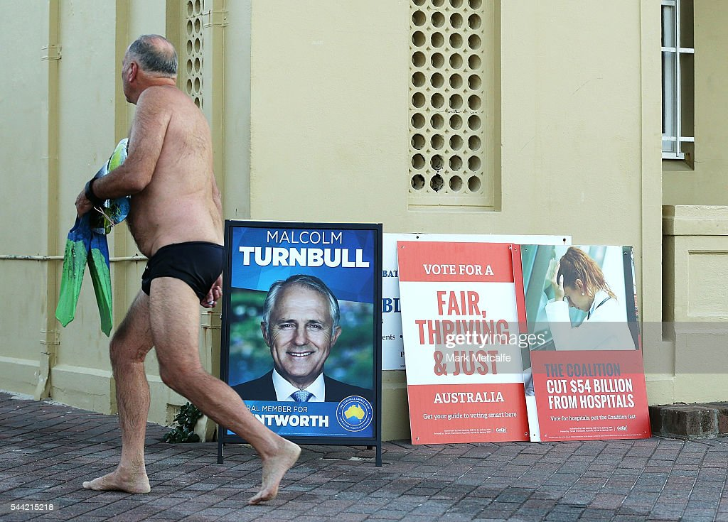 An early morning swimmer walks past election posters at Bondi Beach in the electorate of Wentworth on July 2, 2016 in Sydney, Australia. Voters head to the polls today to elect the 45th parliament of Australia.