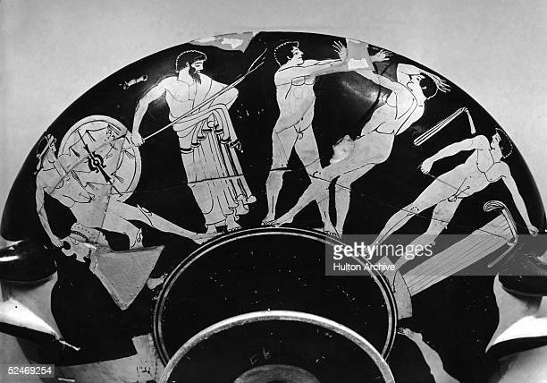 An early Olympiad depicted on an ancient Greek vase or kylix circa 450 BC On the left is a competitor in the Hoplitodromos wearing greaves a helmet...