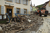 An earth mover collects boulders and other debris that cover a street in the village center next to the Town Hall following a furious flash flood the...