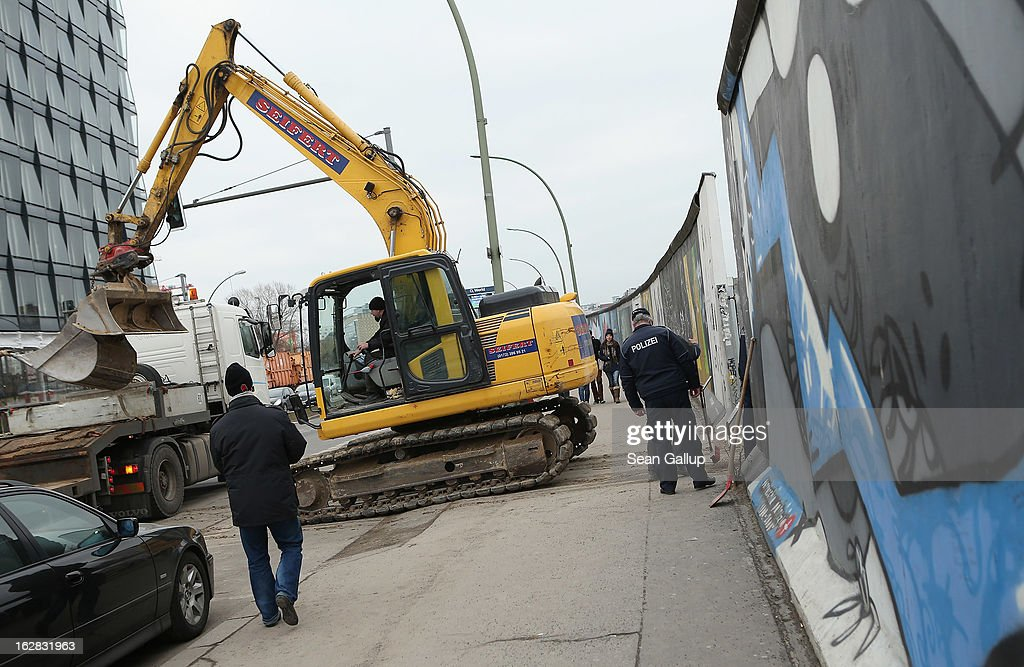 An earth mover emrges from a construction site next to the East Side Gallery, which is the longest still-standing portion of the former Berlin Wall, where a new hotel is scheduled to be built on February 28, 2013 in Berlin, Germany. According to media reports the developer in charge of the project plans to remove an approximately 25-meter long piece of the Wall and transfer it elsewhere in order to allow access to the construction site. Critics, including East Side Gallery mural artists and Spree River embankment development opponents, decry the move, citing the East Side Gallery's status as a protected landmark and a majortourist attraction.