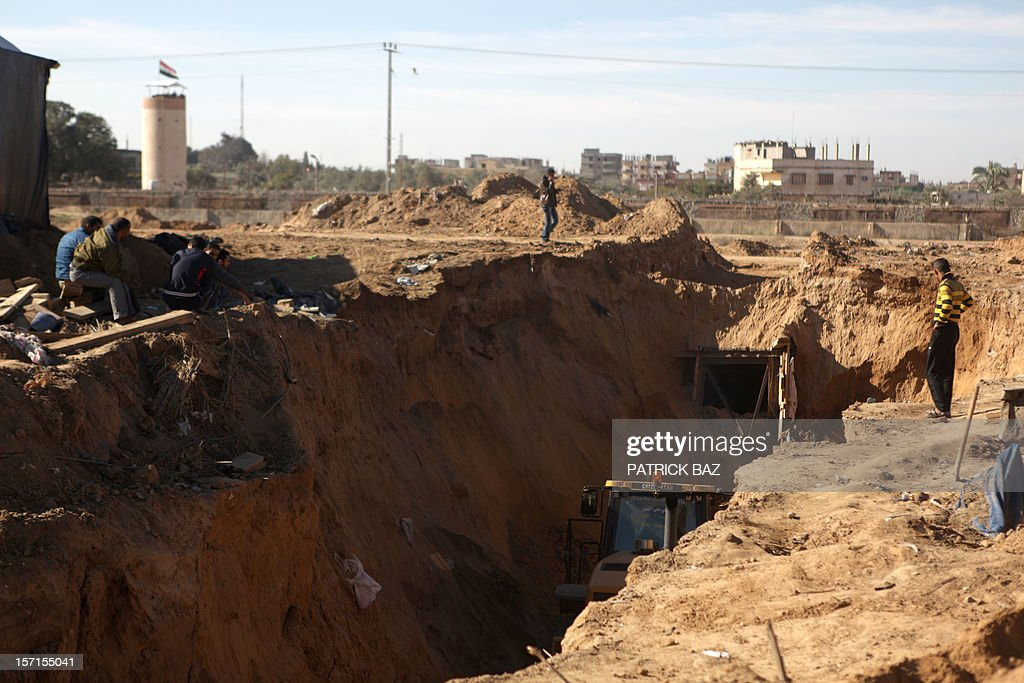 An earth mover repairs a bombed smuggling tunnel linking the Gaza Strip to Egypt, as an Egyptian border guard watchtower is seen in the background (L), in Rafah, on November 29, 2012. Israeli airforce jets bombed most of the smuggling tunnels in the southern Gaza Strip during its war against the Islamist movement Hamas, which rules the coastal Palestinian territory, between 14 to 21 of November 2012. AFP PHOTO / PATRICK BAZ