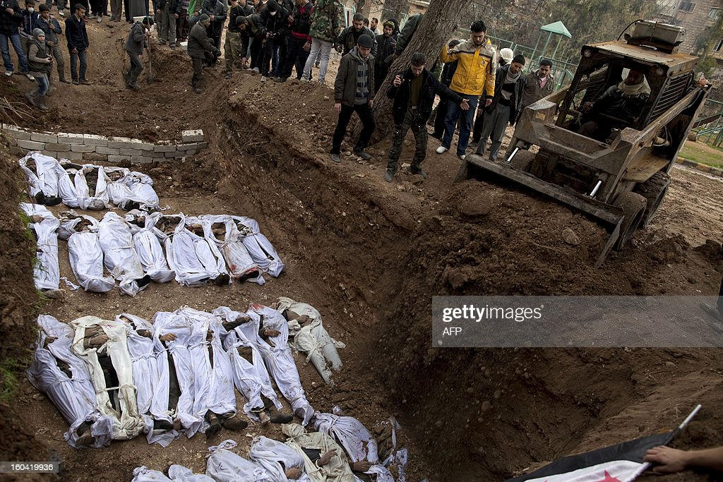 An earthmover pours soil on the bodies of Syrian civilians, who were executed and dumped in the Quweiq river, during their burial at a park now renamed 'Martyrs of the River' park in the Bustan al-Qasr district of the northern city of Aleppo on January 31, 2013. The bodies of dozens of young men, all executed with a single gunshot, were found in the river this week, adding to the grim list of massacres committed during Syria's 22-month conflict. AFP PHOTO/JM LOPEZ