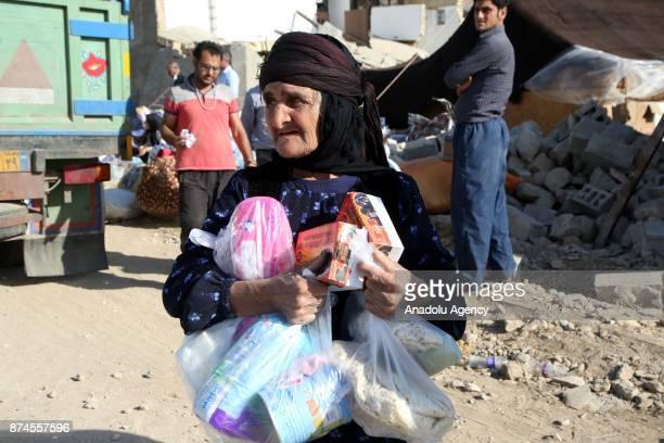 An earthquake survivor woman carries humanitarian aid in Kuik village of Kermanshah Iran on November 15 2017 Homeless people who live in Kuik village...