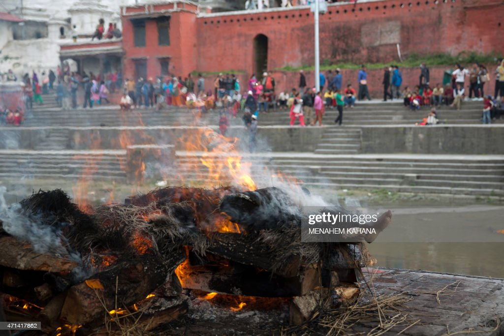 An earthquake victim's body burns during a cremation ceremony in the Pashupatinata temple in Kathmandu on April 28 2015 Hungry and desperate...