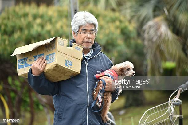An earthquakeaffected evacuee holds his dog as he carries relief supplies in Mashiki Kumamoto prefecture on April 17 2016 Rescuers were racing...