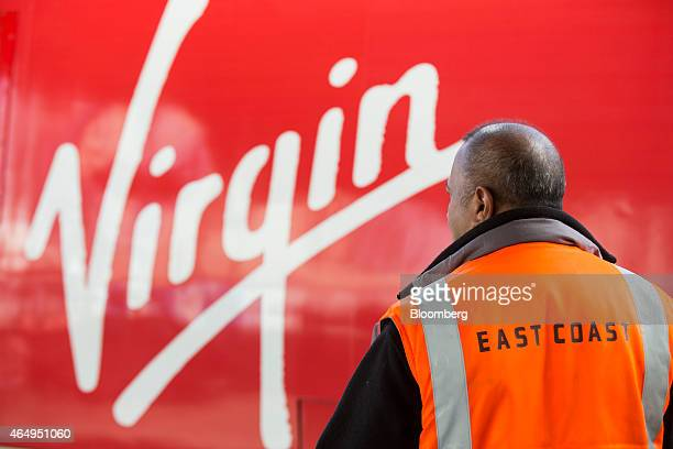 An East Coast railway engineer stands on the railway platform alongside a Virgin Trains East Coast train operated by Virgin Trains ahead of departure...