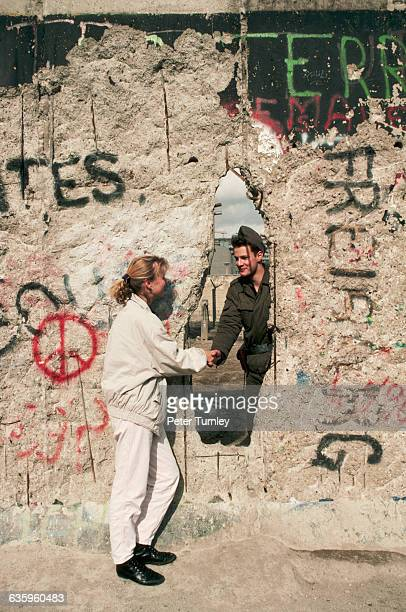 An East German border guard shakes hands with a West German woman through a hole in the Berlin Wall