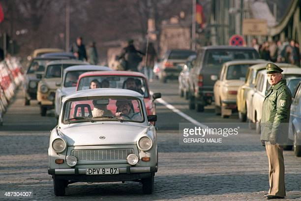 An East German policeman looks at East German Trabant cars as heavy East to West traffic clogged the Glienicker Bridge the bridge where East West spy...
