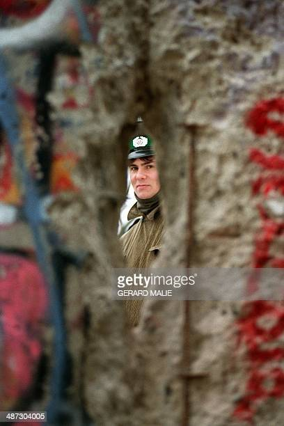An East German policeman looks through a hole made in the Berlin Wall next to the Brandebourg Gate on November 21 1989 On November 09 Gunter...