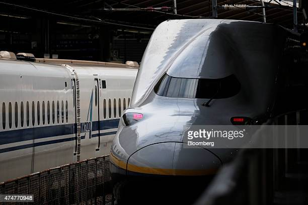 An East Japan Railway Co E4 series Shinkansen bullet train right approaches Tokyo Station while a Central Japan Railway Co N700 series Shinkansen...