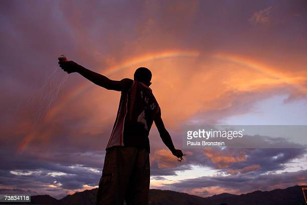 An East Timorese man fishes against the backdrop of a rainbow at sunset on April 7 2007 in Dili East Timor The population of East Timor will go to...