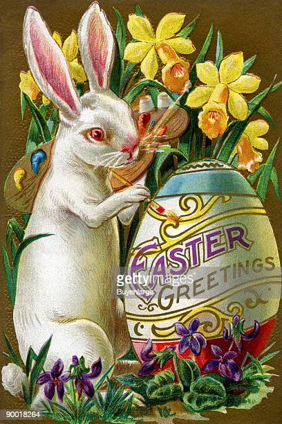 An Easter bunny rabbit paints an Easter Greetings egg within a flower garden