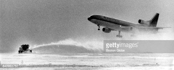 An Eastern Air Lines flight takes off at Logan Airport in Boston after it reopened following a snow storm on Jan 11 1984 Crews continue to clear snow...