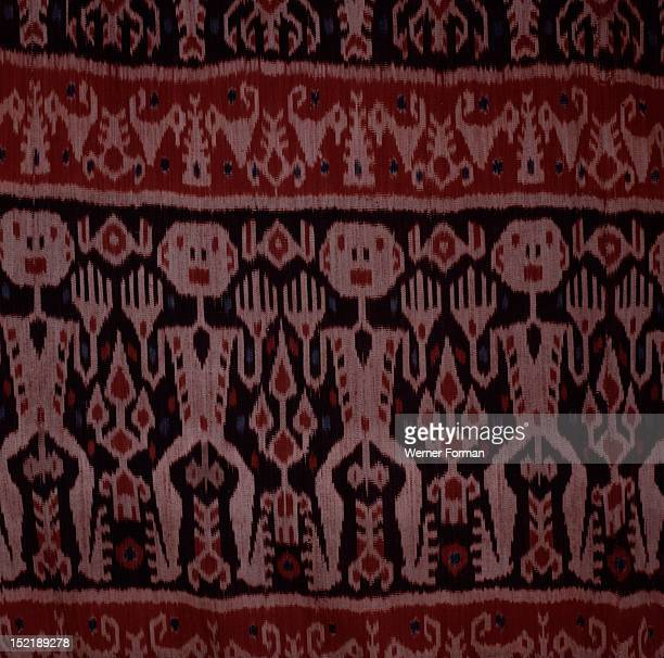 An Eastern Sumba noblemans mantle hinggi decorated by warp ikat dying the threads prior to weaving The male figures depicted may be ancestors or...