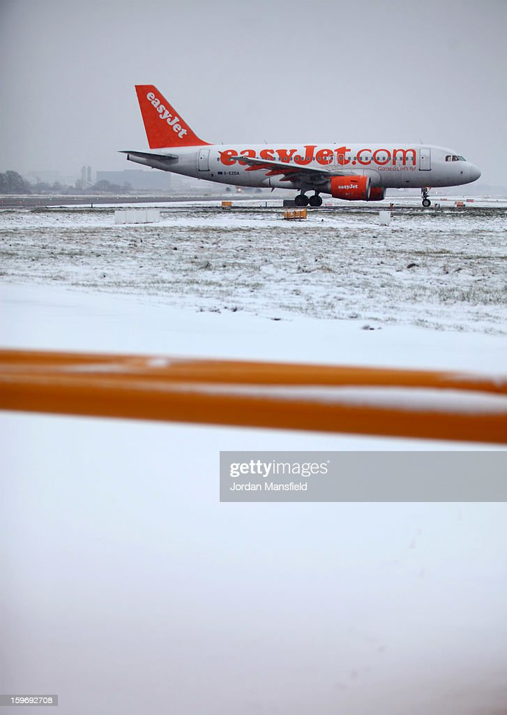 An Easyjet plane sits at the end of the runway waiting to take-off at London Gatwick Airport on January 18, 2013 in London, United Kingdom. Widespread snowfall is affecting most of the UK with school closures and transport disruption. The Met Office has issued a red weather warning for parts of Wales, advising against all non-essential travel as up to 30cm of snow is expected to fall in some areas today.