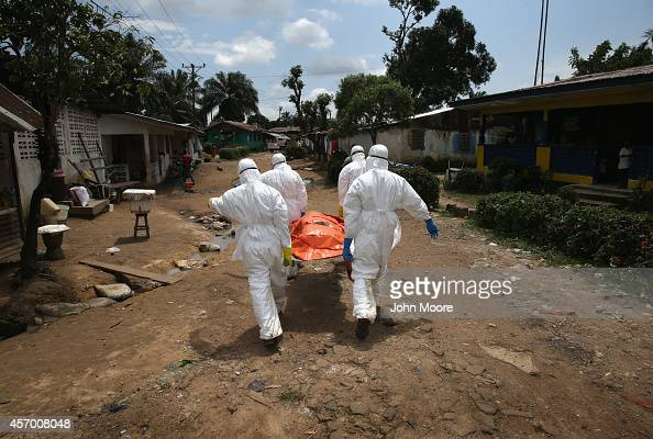 An Ebola burial team carries the body of a woman through the New Kru Town suburb on October 10 2014 of Monrovia Liberia The World Health Organization...