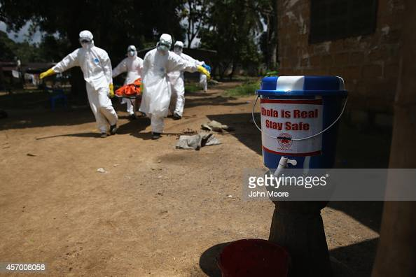An Ebola burial team dressed in protective clothing carries the body of a woman while passing a bucket of chlorinated water for hand washing in the...