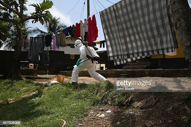 An Ebola burial team member cuts through a yard to collect the body of a woman in the New Kru Town suburb on October 10 2014 of Monrovia Liberia The...