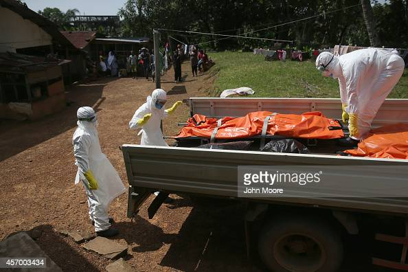 An Ebola burial team removes the body of Nama Fambule for cremation on October 10 2014 in Monrovia Liberia Family members and neighbors said that she...