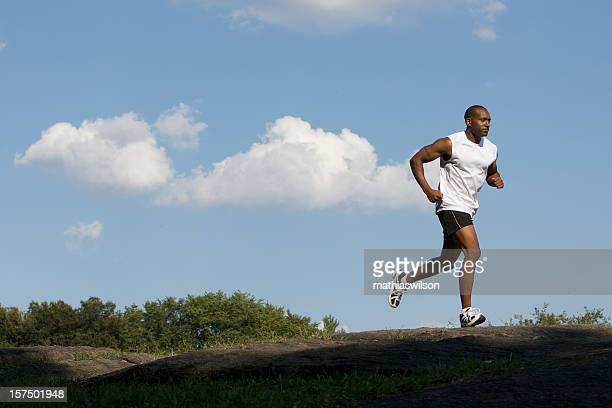 An ebony man in fitness clothing running outdoors