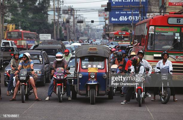 An eclectic mass of traffic including motorcycles threewheeler tuk tuk taxis buses cars and pickups wait at a light in Bangkok