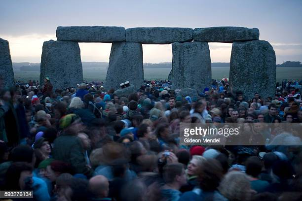 An eclectic mix of partygoers revellers hippies hedonists pagans druids and drummers gather within the stone circle of Stonehenge to welcome the...
