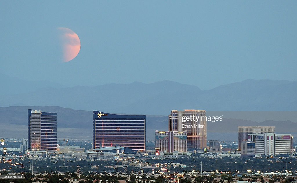 An eclipsed supermoon rises behind the Las Vegas Strip on September 27 2015 in Las Vegas Nevada A supermoon occurs when a full moon coincides with...