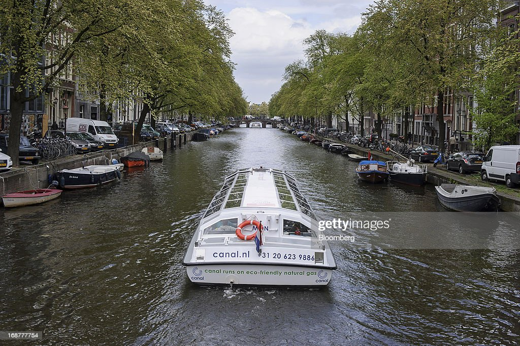 An eco-friendly Canal Bus, operated by the Canal Company B.V., is seen traveling along a canal in the Dutch city of Amsterdam, Netherlands, on Tuesday, May 14, 2013. Euro-area data this week will probably reveal economic scars of the sovereign debt crisis confirming that the region is now suffering the longest recession since the single currency's creation. Photographer: Jock Fistick/Bloomberg via Getty Images