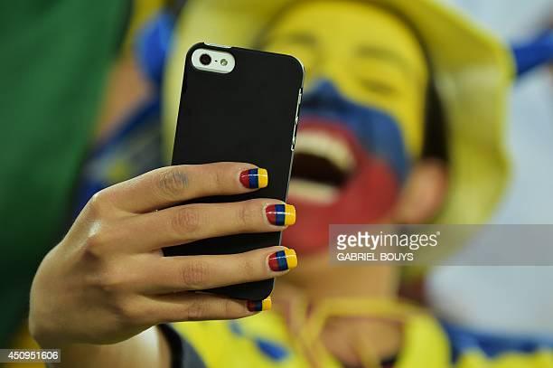 An Ecuador supporter takes a selfie prior to a Group E football match between Honduras and Ecuador at the Baixada Arena in Curitiba during the 2014...