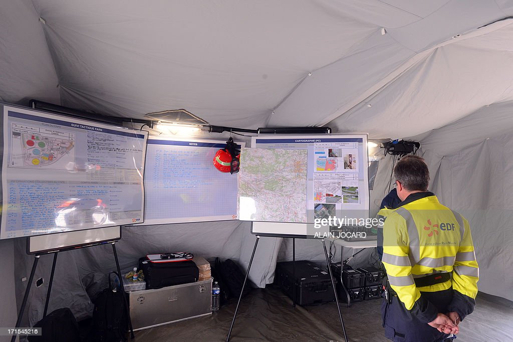 An EDF new rapid response nuclear task force (FARN) member stands in front of action plans during a simulation of a nuclear accident at the Avoine nuclear reactor near Chinon, western France, on June 26, 2013. By the end of 2014, the FARN task will be capable of intervening at all the reactors on one EDF site simultaneously in France in an emergency. AFP PHOTO / ALAIN JOCARD
