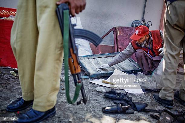 An Edhi foundation rescue worker picks up a pair of broken glasses whilst searching for body parts at the site of a suicide bomb blast on November 19...