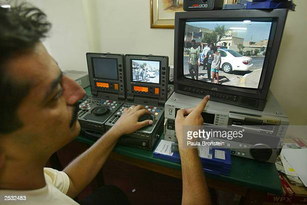 An editor at AlArabiya news Channel works on a satellite feed of a video tape to Dubai September 24 2003 in Baghdad Iraq Iraq's Governing Council...
