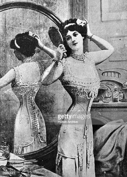 An Edwardian lady wearing a tightlylaced corset performs her toilette in front of the mirror Original Publication A magazine advertisement for the...