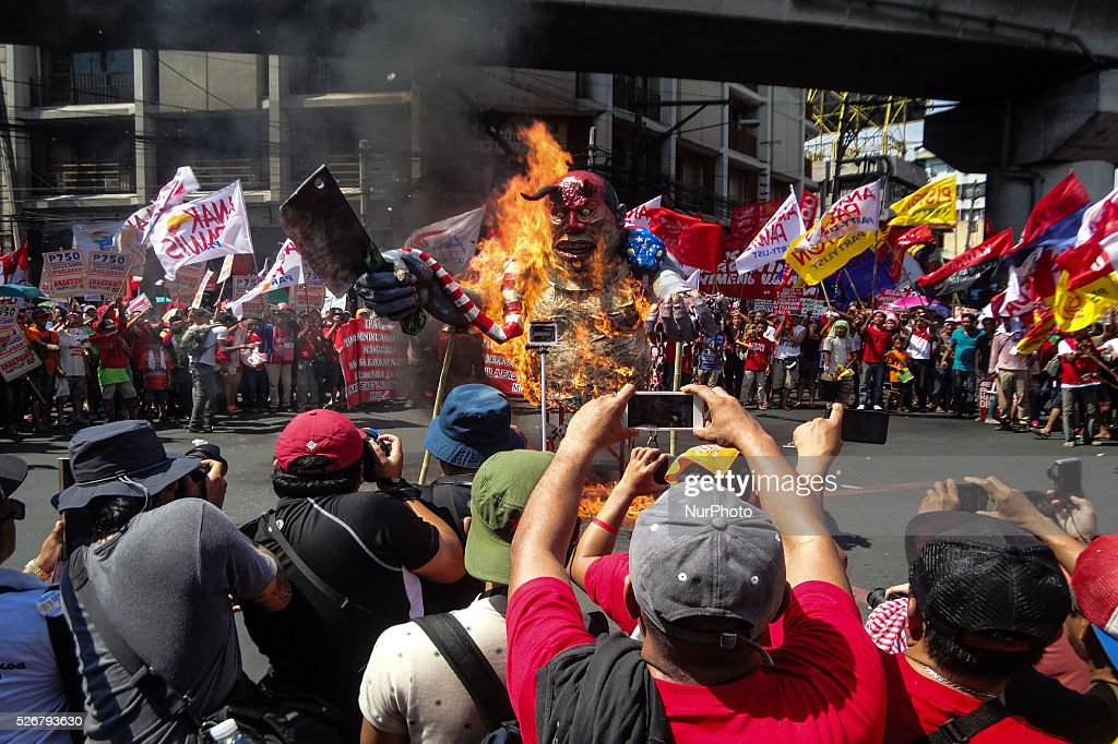 An effigy depicting President Benigno Aquino III as a butcher burns during a rally commemorating Labor Day in Manila on Sunday, May 1, 2016. Thousands of protesters marched to protest the government's labour policy and demand higher wages amid rising prices for basic commodities.