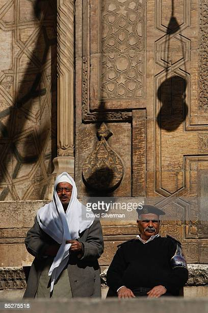 An Egyptain policeman and a mosque caretaker wait for tourists at the richly decorated entrance to the Mamluk 14th century madrasa and mausoleum of...