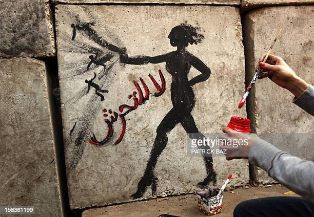 An Egyptian activist draws graffiti depicting a woman and reading in Arabic 'No to Sexual Harassement' on a wall outside the presidential palace in...