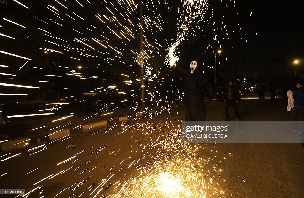 An Egyptian activist ignites fireworks following a performance by Egyptian activists and youth of the internet craze 'Harlem Shake' in front of the Muslim Brotherhood headquarters in Cairo on February 28, 2013.