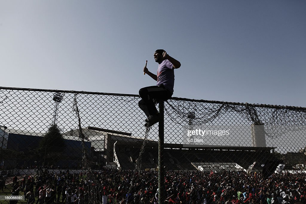 An Egyptian 'Ahly Ultra' cheers while climbing over a fence at the Al Ahly home stadium during celebrations after the announcement that 21 fans of the Al Masry football club involved in a football stadium massacre last year were sentence to death on January 26, 2013 in Cairo, Egypt. A verdict was announced Saturday in a case over the deaths of more than seventy fans of Egypt's Al-Ahly football club in a stadium massacre on February 1, 2012, in the northern city of Port Said, during a riot that began minutes after the final whistle of a match between Al-Ahly and Al-Masry. 21 fans of the Al Masry football club were given the death penalty in the court case, a verdict that must now be approved by Egypt's Grand Mufti. The verdict was handed down during a period of high tension across Egypt, one day after the second anniversary of the beginning of Egypt's 2011 revolution that overthrew the regime of former President, Hosni Mubarak.