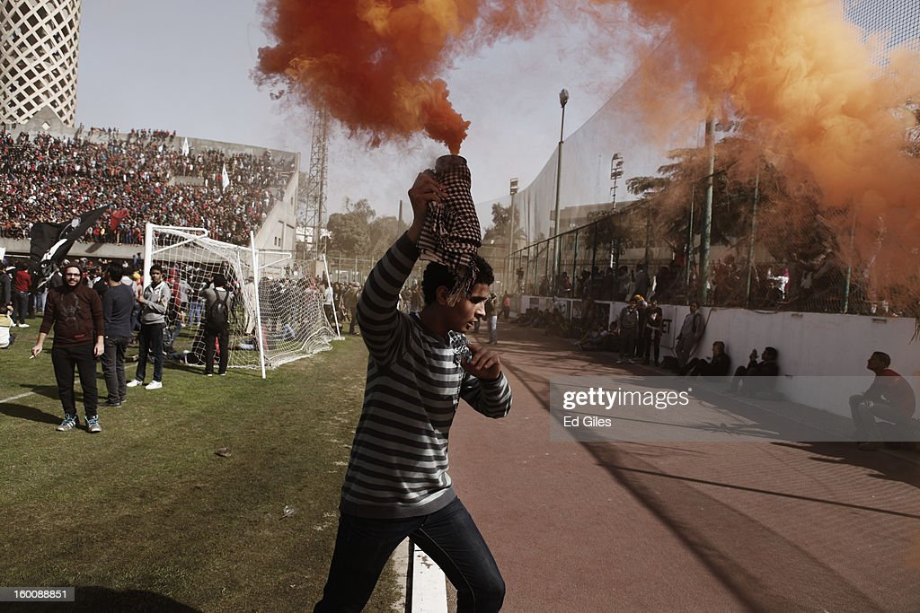 An Egyptian 'Ahly Ultra' soccer fan holds a smoke flare above his head during celebrations after the announcement that 21 fans of the Al Masry football club involved in a football stadium massacre last year were sentence to death on January 26, 2013 in Cairo, Egypt. A verdict was announced Saturday in a case over the deaths of more than seventy fans of Egypt's Al-Ahly football club in a stadium massacre on February 1, 2012, in the northern city of Port Said, during a riot that began minutes after the final whistle of a match between Al-Ahly and Al-Masry. 21 fans of the Al Masry football club were given the death penalty in the court case, a verdict that must now be approved by Egypt's Grand Mufti. The verdict was handed down during a period of high tension across Egypt, one day after the second anniversary of the beginning of Egypt's 2011 revolution that overthrew the regime of former President, Hosni Mubarak.
