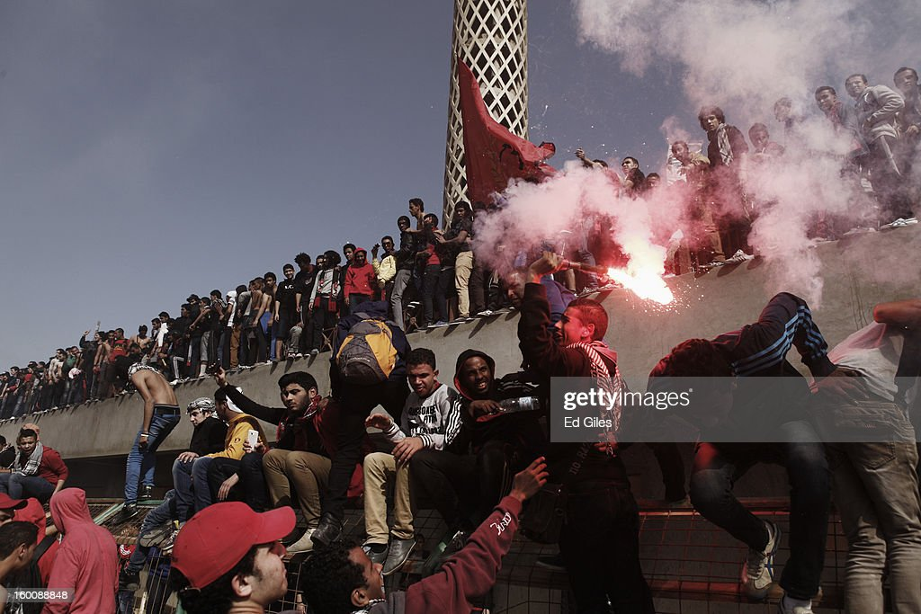 An Egyptian 'Ahly Ultra' soccer fan swings a live flare above his head during celebrations after the announcement that 21 fans of the Al Masry football club involved in a football stadium massacre last year were sentence to death on January 26, 2013 in Cairo, Egypt. A verdict was announced Saturday in a case over the deaths of more than seventy fans of Egypt's Al-Ahly football club in a stadium massacre on February 1, 2012, in the northern city of Port Said, during a riot that began minutes after the final whistle of a match between Al-Ahly and Al-Masry. 21 fans of the Al Masry football club were given the death penalty in the court case, a verdict that must now be approved by Egypt's Grand Mufti. The verdict was handed down during a period of high tension across Egypt, one day after the second anniversary of the beginning of Egypt's 2011 revolution that overthrew the regime of former President, Hosni Mubarak.