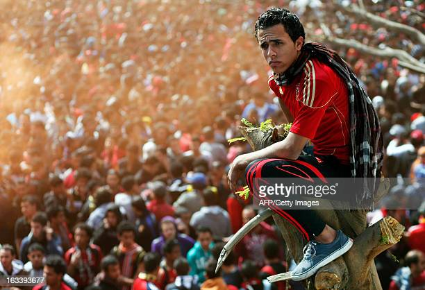 An Egyptian alAhly football club supporter sits on top of tree stump in Cairo on March 9 as he awaits the verdict of the court over a deadly football...