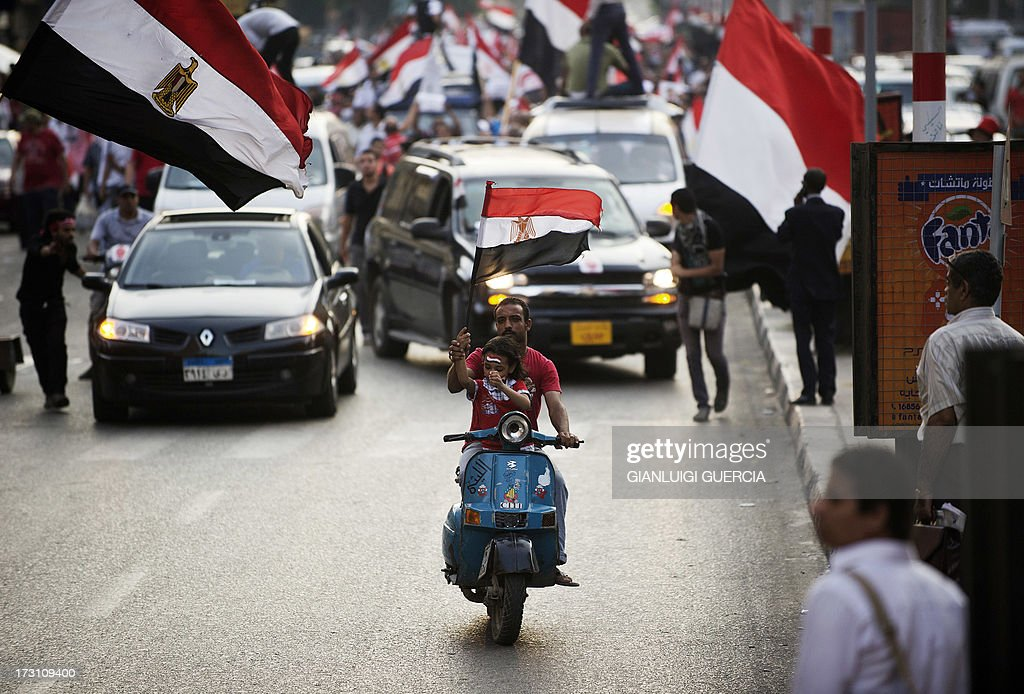 An Egyptian and his daughter wave a national flag riding a Vespa in front of police vehicles and protesters marching towards Egypt's landmark Tahrir square against deposed president Mohamed Morsi on July 7, 2013 in Cairo. A sea of flags fluttered wildly as tens of thousands of people staged a show of force in Cairo's Tahrir Square to back the army's ouster of Egypt's first freely elected president. AFP PHOTO/GIANLUIGI GUERCIA