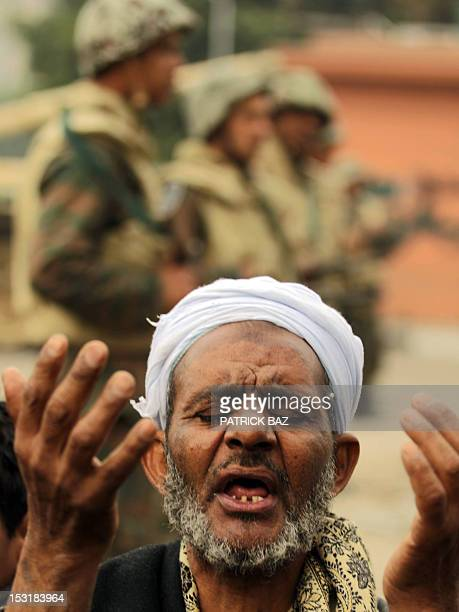 An Egyptian antigovernment demonstrator and a member of the Egyptian Muslim Brotherhood movement prays in front of Egyptian soldiers at Cairo's...