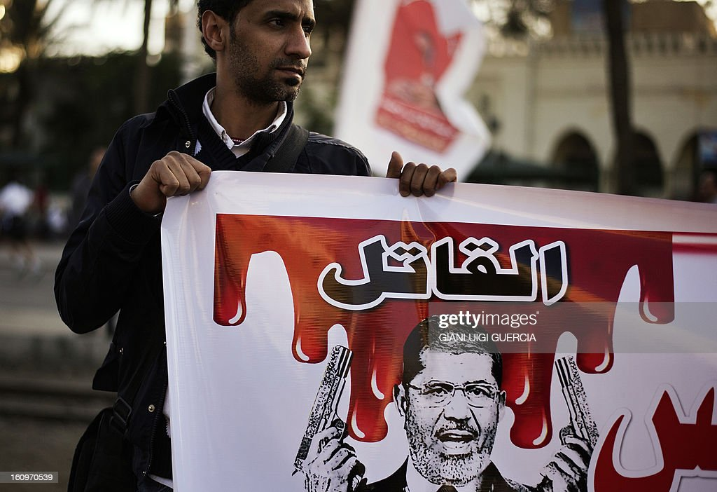 An Egyptian anti-government protester holds a poster mocking Egypt's President Mohamed Morsi during a demonstration outside the presidential palace in Cairo on February 8, 2013. Thousands took to the streets across Egypt after opposition groups called for 'Friday of dignity' rallies demanding Morsi fulfill the goals of the revolt that brought him to power. AFP PHOTO/GIANLUIGI GUERCIA