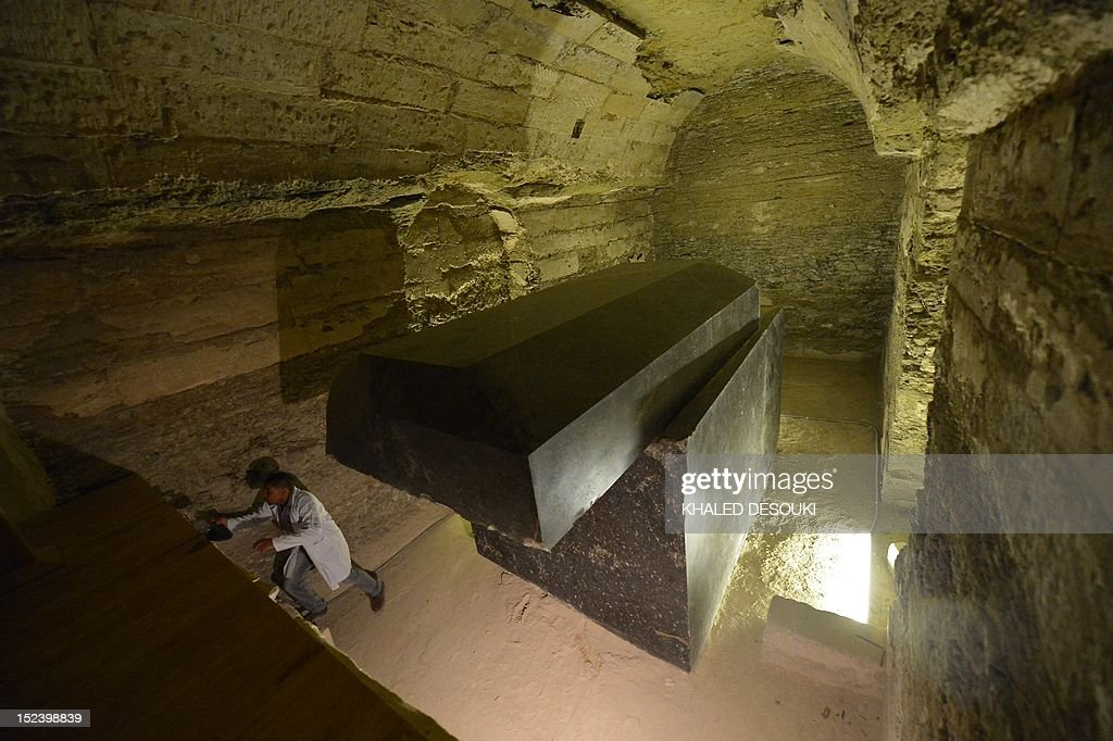 An Egyptian archeologist walks next to a tomb at the Serapeum of Saqqara, a vast underground necropolis south of Cairo dedicated to the bulls of Apis, as it reopens to the public after 11 years of renovation, on September 20, 2012 . The Serapeum, whose origin dates back to around 1400 BC, was discovered in 1851 by French Egyptologist Auguste Mariette, founder of the first department of Egyptian antiquities. The site contains huge subterranean galleries in which are contained the large tombs of some 30 sacred bulls, accompanied by steles bearing inscriptions providing information on the reigns under which the animals lived.